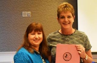 Janie DeJesus awards Melinda Cordova, Secretary a new pink binder.