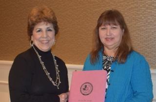 Janie DeJesus Awards Mary Garrison, President a new pink binder
